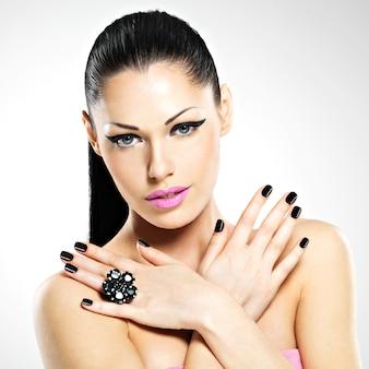 Volto della bella donna sexy con unghie nere e labbra rosa. ragazza sexy con il trucco di moda