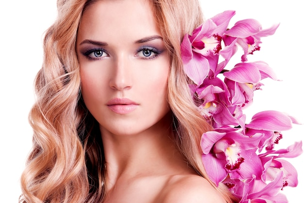Face of beautiful woman with healthy skin and pink flower over white wall.
