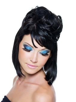 Volto di una bellissima giovane donna con trucco blu brillante. isolato su bianco