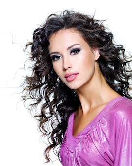 Il volto di una giovane e bella donna con i capelli lunghi riccioli marroni e la moda scura si compongono. isolato su bianco