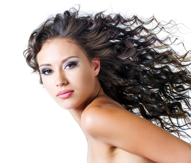 Face of  a beautiful young woman with brown long ringlets hairs and dark fashion make up. isolated on white