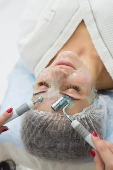 フェイスビューティートリートメント。高周波ダルソンバルを使用して顔のダーソンバル療法を受ける女性