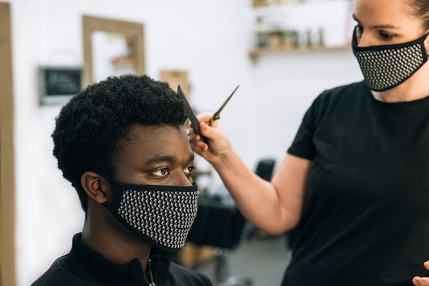 Face of a black guy getting a haircut in a hair salon with a black mask on his face from the coronavirus. the hairdresser also wears a mask. the hair has it like the afro