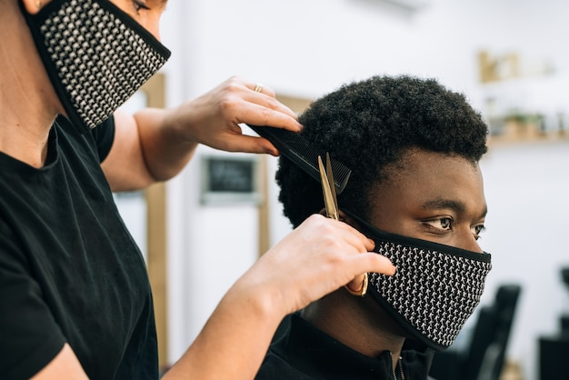 Face of a black guy getting a haircut in a hair salon with a black mask on his face from the coronavirus.