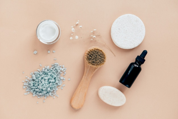 Face and body care products flat lay on beige background