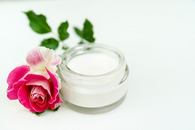 Face and body cream with pink rose isolated on white