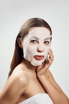 얼굴 관리 및 미용 치료. 천 보습 마스크를 가진 여자입니다. 미용 절차. 스파 및 미용