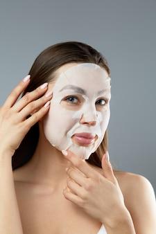 얼굴 관리 및 미용 치료. 그녀의 얼굴에 천 보습 마스크를 가진 여자. 미용 절차. 소녀 뷰티 스파 및 미용.