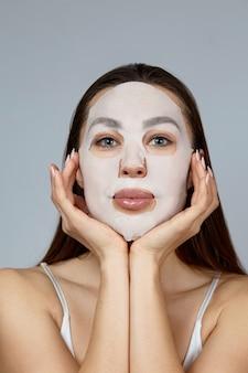 얼굴 관리 및 미용 치료. 그녀의 얼굴에 천 보습 마스크를 가진 여자. 미용 절차. 스파 및 미용.