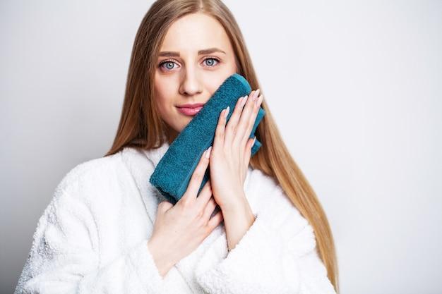 フェイスケア、シャワーを浴びた後、美しい女性がタオルで顔を拭きます。