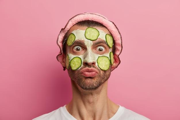 얼굴 관리 개념. 충격을받은 감정적 인 남자가 자신의 반사에 도청 된 눈으로 응시하고 오이 조각으로 흰색 점토 마스크를 적용합니다.