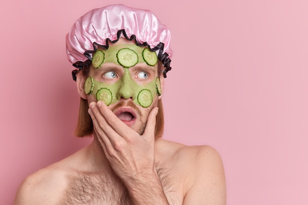 Face care concept. stunned young man applies moisturizing beauty green mask holds chin stares surprisingly aside