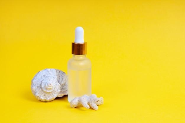Уход за лицом в стеклянной бутылке-капельнице с морской раковиной и кораллами на желтом фоне. концепция ухода за кожей.