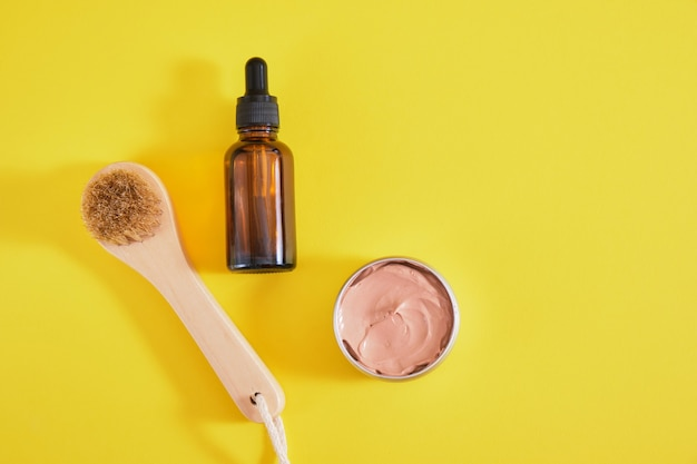 Face care set, cosmetic clay, wooden massage brush and amber dropper bottle, yellow background top view copy space