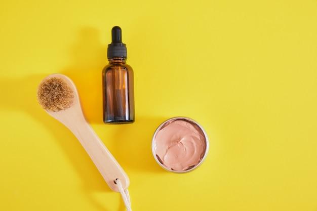 フェイスケアセット、化粧用粘土、木製マッサージブラシ、琥珀色のスポイトボトル、黄色の背景上面図コピースペース