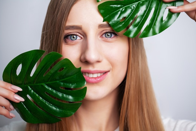Уход за лицом, молодая женщина, держащая зеленый лист возле здоровья кожи лица.