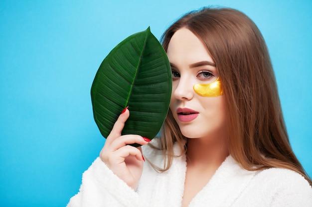 얼굴 관리, 얼굴 피부 건강 근처 녹색 잎을 들고 젊은 여자.