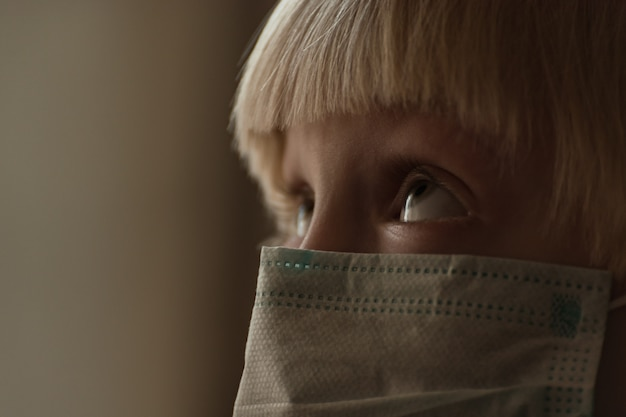 Face of child in medical mask close up. boy wears surgical mask protection against flu
