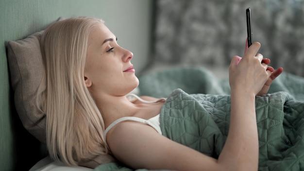 호텔 방의 침대에 편안하게 누워있는 동안 두 손을 사용하여 휴대 전화에 메시지를 입력하는 여자의 얼굴 클로즈업.