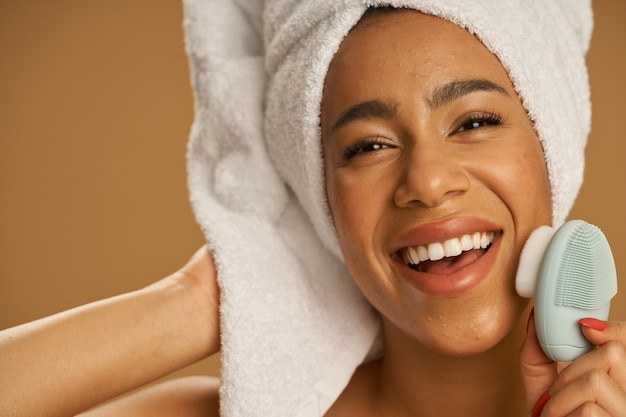 Face closeup of joyful young woman after shower looking excited at camera
