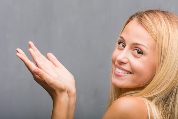 Face closeup, portrait of a natural young blonde woman holding something with hands