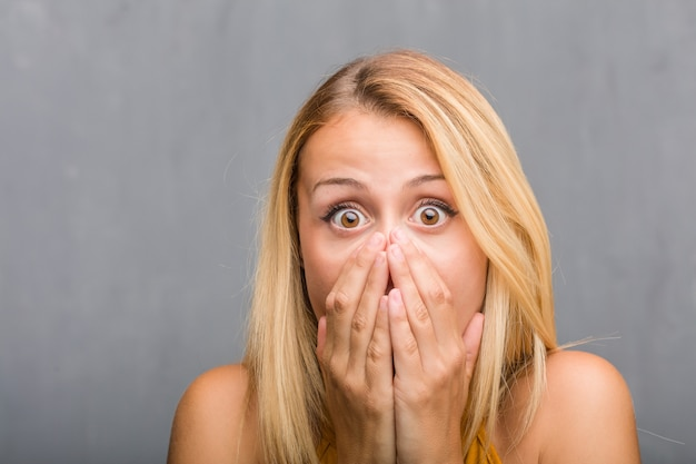 Face closeup, portrait of a natural young blonde woman very scared and afraid