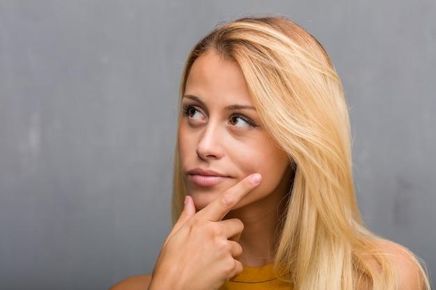 Лицо крупным планом, портрет натуральной молодой блондинки, сомневающейся и смущенной, думающей об идее или обеспокоенной чем-то