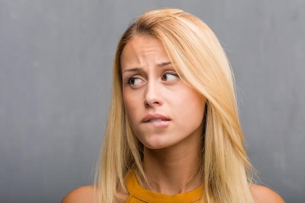 Смотрите на крупный план, портрет естественной молодой белокурой женщины сомневаясь и смущенный.