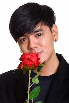 Face of cool handsome asian man smelling red roses