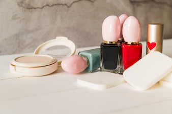 Face cosmetic compact makeup powder with sponges; nail polish bottle and lipstick on table