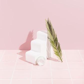 타일이 있는 파스텔 핑크 배경에 얼굴 크림과 녹색 잎. 하나의 흰색 물결 모양의 3d 개체입니다.