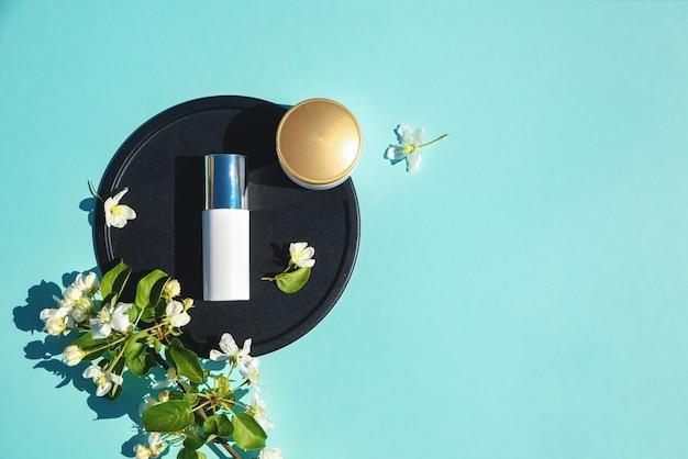 얼굴 크림, 뷰티 플랫을위한 엘릭서는 꽃이있는 파란색 테이블에 놓여 있습니다. 천연 유기농 화장품과 향수의 개념. 미니멀리즘