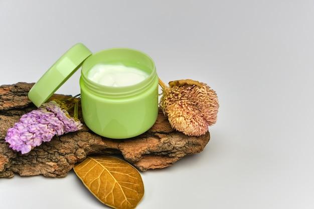 Крем для лица в зеленой банке на коре дерева с засушенными цветами, белый фон. концепция натуральной косметики. Premium Фотографии