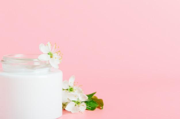 白い花とピンクの背景の白い瓶にフェイスクリーム。コンセプト自然派化粧品、オーガニック美容。スペースをコピーします。