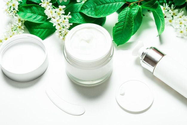 Face cream in jar on white table with bird cherry