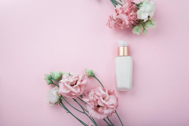 신선한 분홍색과 흰색 꽃으로 얼굴 크림, 복사 공간이 많은 분홍색 배경에 flatlay. 피부 관리 및 노화 방지 화장품 컨셉