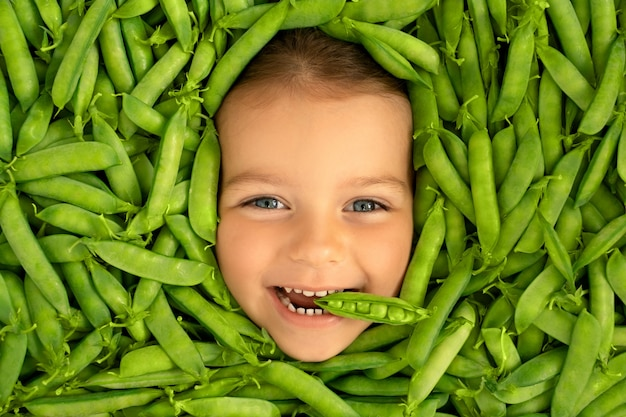 The face of a cute funny child surrounded by green pods of fresh ripe peas