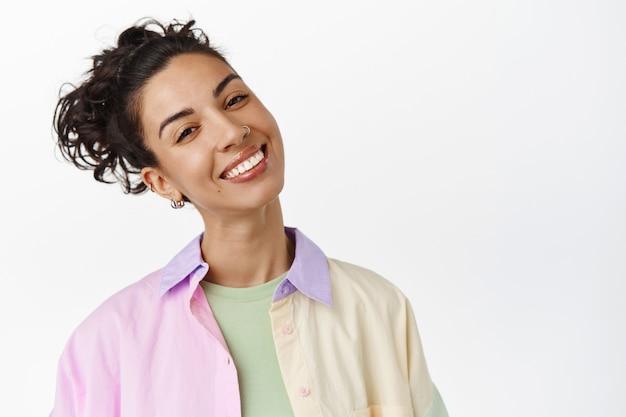 Volto di ragazza bruna felice con capelli ricci pettinati, testa inclinata e sorridente gioioso e positivo, in piedi su bianco.