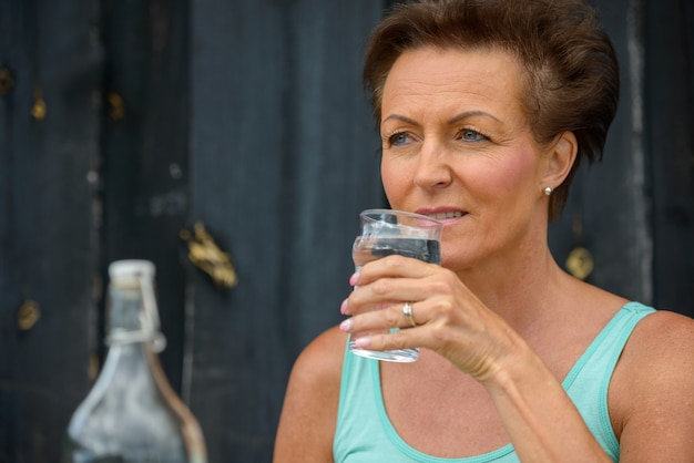 Face of happy mature beautiful woman thinking while drinking water at restaurant outdoors