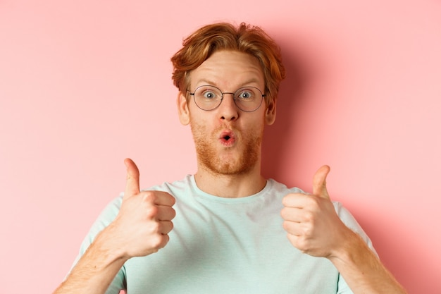 Face of happy redhead man in glasses and t-shirt, showing thumbs-up and looking excited, approve and praise cool promotion, standing over pink background.
