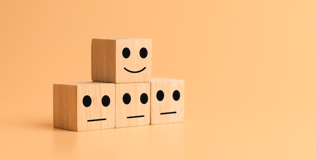 Face happy and sad icon on wooden cube on table. customer service evaluation and satisfaction rating concepts.