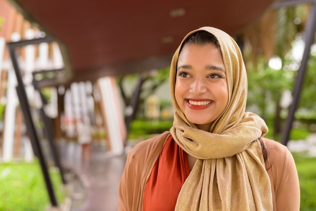 Face of happy young beautiful indian muslim woman thinking in the city with nature