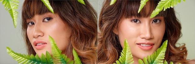 20代のアジア人女性の顔のヘッドショットの肖像画日焼けした肌茶色のブロンドの髪のスタイル化粧品メイク。女の子は感情を表現し、灰色の背景に緑の葉を保持します。