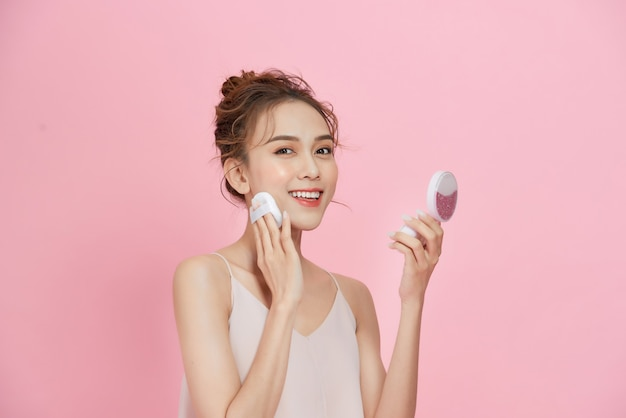 얼굴 화장. 거울을보고 건조 분말 재단을 적용하는 아름 다운 아시아 여성의 근접 촬영.