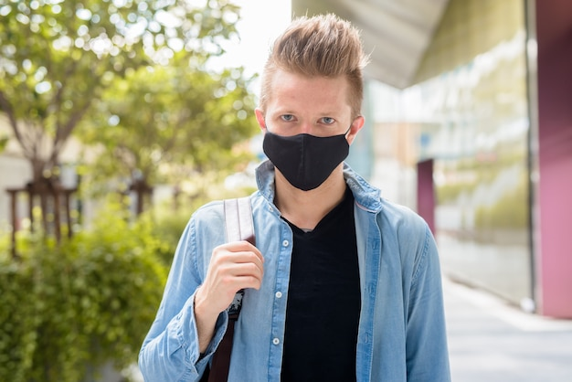 Face of man with backpack wearing mask in the city streets outdoors