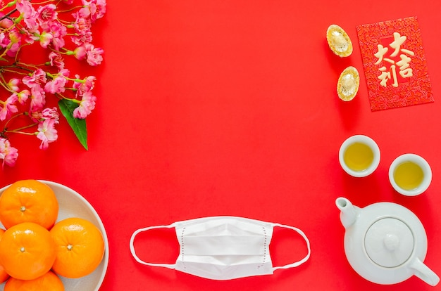 Face mask on chinese new year red background with red envelope packet or ang bao (word means auspice), gold ingots, tea set, oranges and chinese blossom flowers.
