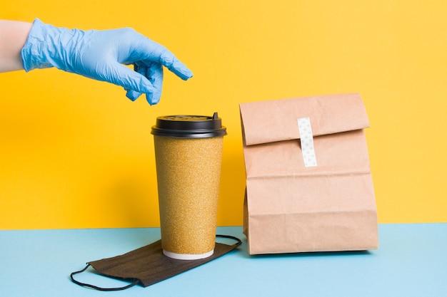 얼굴 마스크, 커피 및 배달 음식 패키지, 노란색 배경 비접촉식 배달 개념에 장갑에 손을