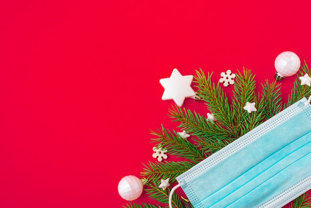 Face mask fir tree and decorations on red background