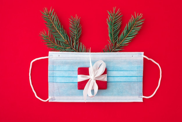 Face mask fir tree gift box and decorations on red background flat lay top view