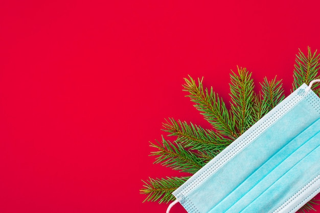 Face mask and fir tree on red background flat lay